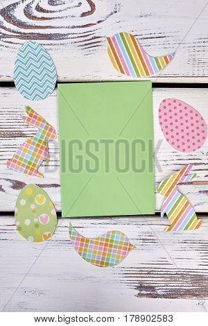 Easter paper cutouts, blank card. Empty green paper on wood. Greet and wish the best.