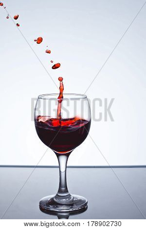 moving red wine glass over a white background on a white background freezing