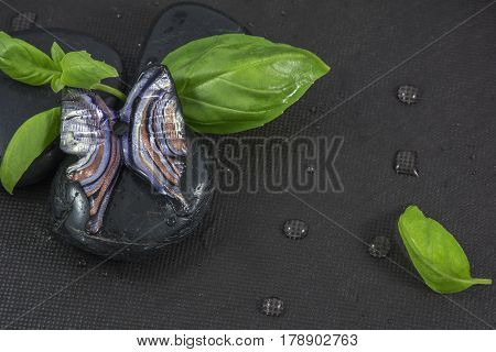 One blue glass butterfly on the black stones with basil leaves on the black background