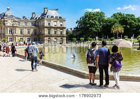 Paris France - Jule 07 2016: Several Parisians stop at the edge of the pool fountain in the Luxembourg Gardens to watch the colorful model sailboats race across the water.
