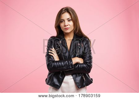 Portrait of irritated woman looking at camera with anger in eye isolated on pink background