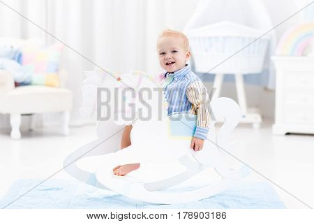 Cute baby boy riding wooden traditional rocking horse toy in white bedroom with pastel rainbow color decoration. Child playing in nursery room. Toys for toddler kid. Interior with crib and chair.