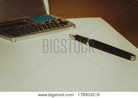 Pen calculator sheet of paper on a brown table business white