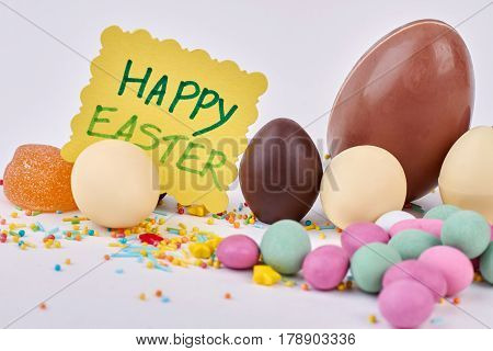 Sweets and Easter greeting card. Chocolate eggs close up. Easter party treats.