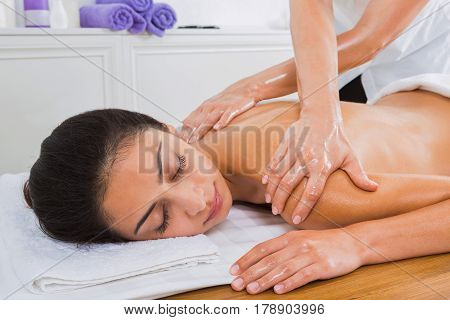 Spa massage therapy. Masseur make body back oil massage to beautiful indian girl in cosmetology cabinet or beauty parlor.