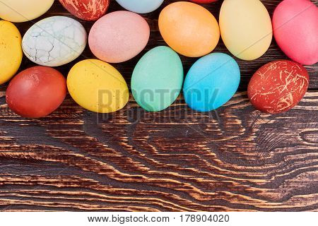 Brown wood background, Easter eggs. Colorful chicken eggs.