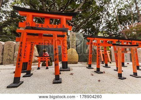 KYOTO, JAPAN - NOVEMBER 10, 2016 : Torii path lined with thousands of torii in the Fushimi Inari Taisha Shrine in Kyoto. Torii is a traditional Japanese gate commonly found in a shrine.