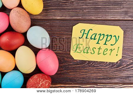 Yellow Easter card and eggs. Painted eggs, brown wooden background.