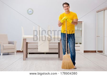 Man husband cleaning the house helping his wife