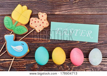Easter eggs, cookies and card. Biscuits with icing on wood. Easter food craft ideas.