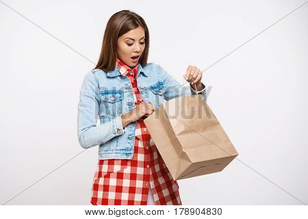 Cheerful young woman in check dress and denim jacket opening paper bag and looking surprised