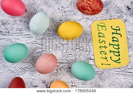 Colored eggs and Easter card. Chicken eggs on painted wood.