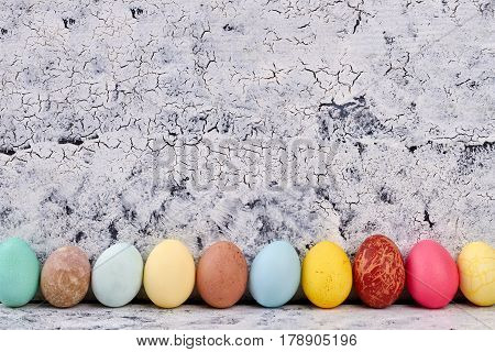 Row of Easter eggs. White painted wood surface.