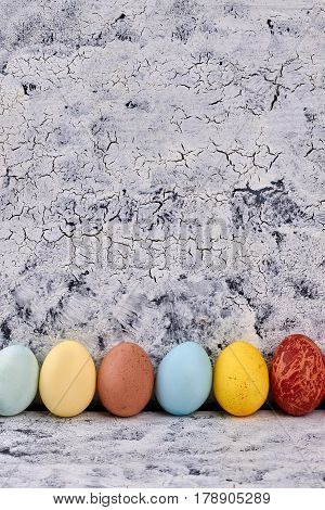 Easter eggs, painted wood background. Row of colored eggs.
