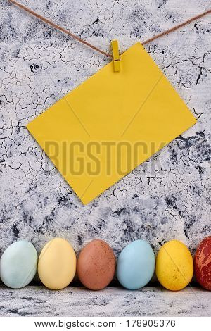 Row of painted chicken eggs. Blank yellow paper on rope.