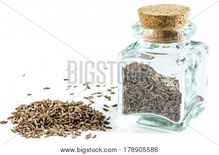 Dry caraway seeds in glass bottle and in a heap isolated on white background. Closeup macro shot.