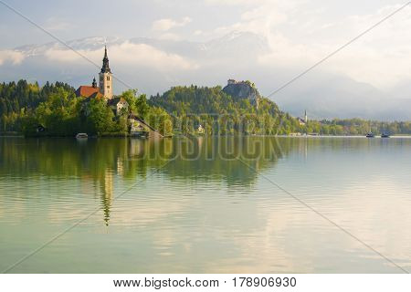 Bled Lake And Pilgrimage Church With Spring Mountain Landscape Background