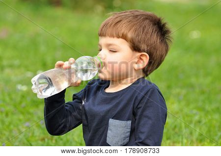 Little boy drinks water from plastic bottle in the park. Boy refresh herself with a cold water