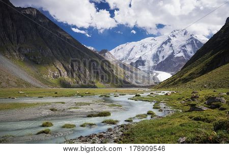 view of a mountain peak with a glacier and a flowing river in Tien Shan mountains