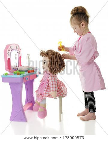 And adorable preschooler spraying her dolls hair as she prepares to style it.  On a white background.