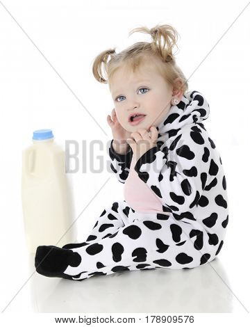 An adorable baby girl wondering what she's doing in a cow outfit sitting by a half gallon of milk.  On a white background.