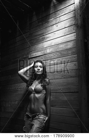 Touching a young woman in jeans and underwear. Wooden background. Brunette girl in underwear. Black-and-white photograph.