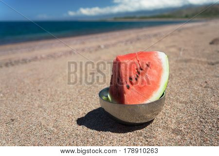 piece of watermelon standing on the beach near blue lake