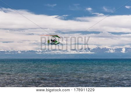 hang-glider hovering over pure emerald water of the lake near mountains