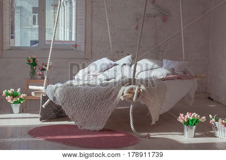 White loft interior in classic scandinavian style. Hanging bed suspended from the ceiling. Cozy large folded beige plaid, giant knit blanket, arm knitting. Trendy room design. Bedroom with tulips