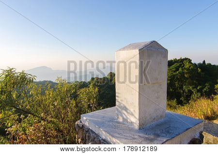 kilometer stone or mile stone with blue sky and trees at mountain.