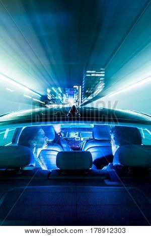 Car, driving through a tunnel, towards a big city, with office buildings, and towers, with people in the back seet and a driver, seen from the bonnet of the car, through the rear window.