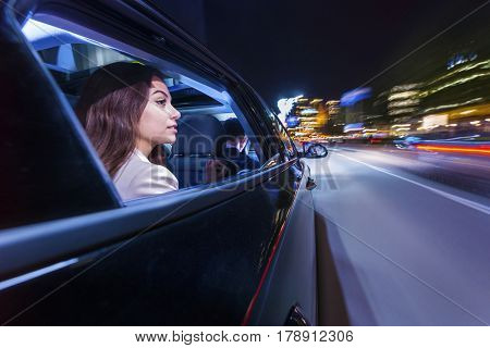 woman sitting in a moving car, looking through her window towards the citylife at night