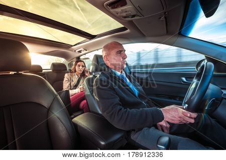 Professional driver, a taxi chauffeur, driving a woman towards her destination.