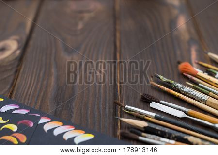 Brushes and sketches are spread out on dark wooden surface