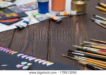 Art brushes and oil paints and sketches are laid out on dark wooden surface