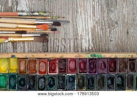 Box with watercolors and brushes on wooden surface