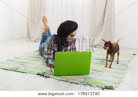 Girl at home with laptop and dog chihuahua. Hipster freelancer woman works at home. Home office, freelance.