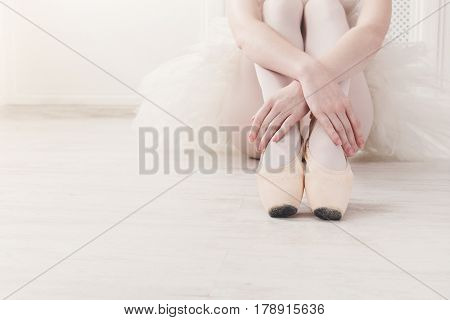 Closeup of ballerina legs, sit in pointe shoes at white wooden floor background, with copy space. Ballet practice. Beautiful slim graceful feet of ballet dancer.