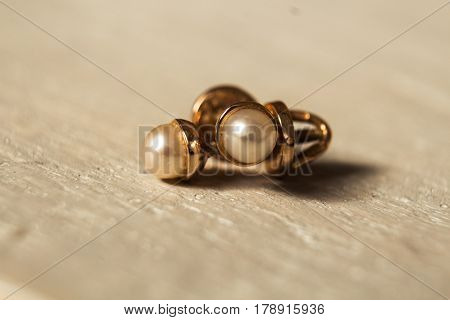 gold earrings with pearls on wooden background