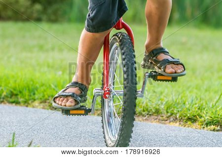 outdoor portrait of young boy riding a unicycle (one wheel bike) on natural background