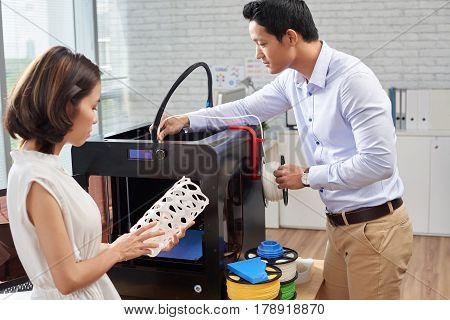 Architect loading white filament in 3D printer