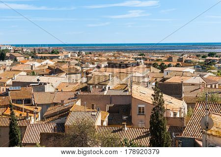 View of typical Mediterranean rooftops with terracotta tiles contrast with blue of sea in coastal town Gruissan France.