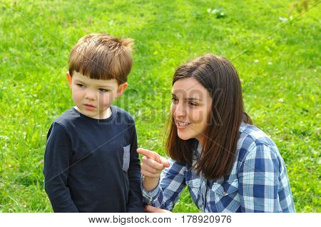 Mother pointing son where to look, Happy mom and son play in the park in spring.