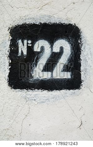 Stencilled number twenty two in black on white plaster wall
