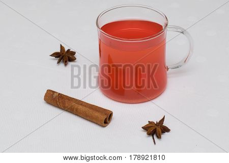 red cranberry drink with cinnamon stick and anise