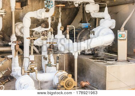 Close up of container with liquid nitrogenCold metal pipe smoking from transferring liquid nitrogen