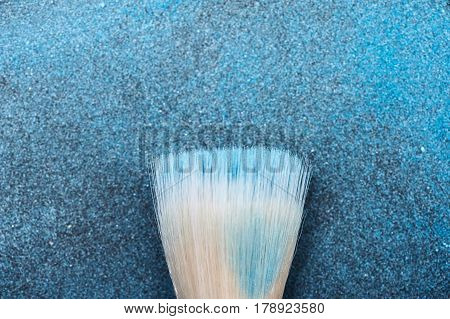 Make-up Brush Tool on blue Cosmetics Particles