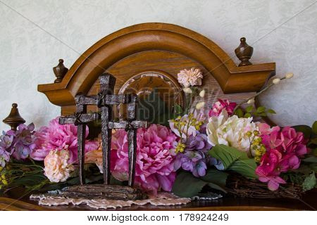 Three crosses of Calvary in front of spring silk flowers on top of antique server.