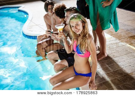 Young cheerful friends smiling, rejoicing, drinking cocktails, resting at party near swimming pool. Copy space.