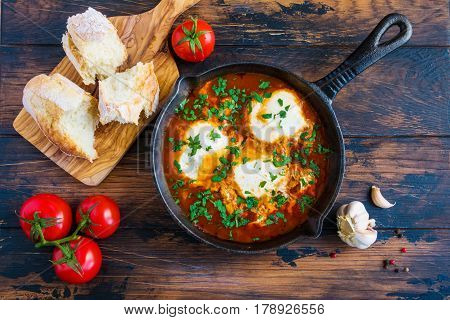 Shakshouka or shakshuka poached eggs in a sauce of tomatoes beans onion and spices in a black cast iron skillet on the wooden table top view.